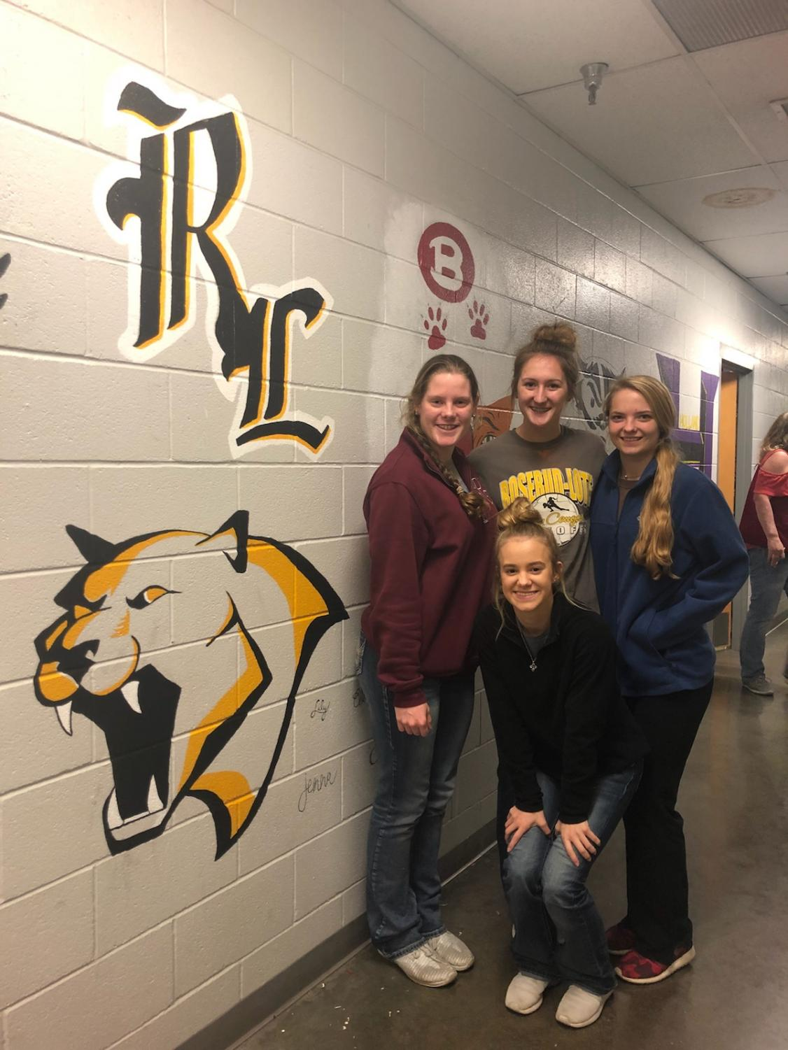 Clara Coker, Jenna Kleypas, Christa Niemeyer and Lily Dawson pose next to their artwork.