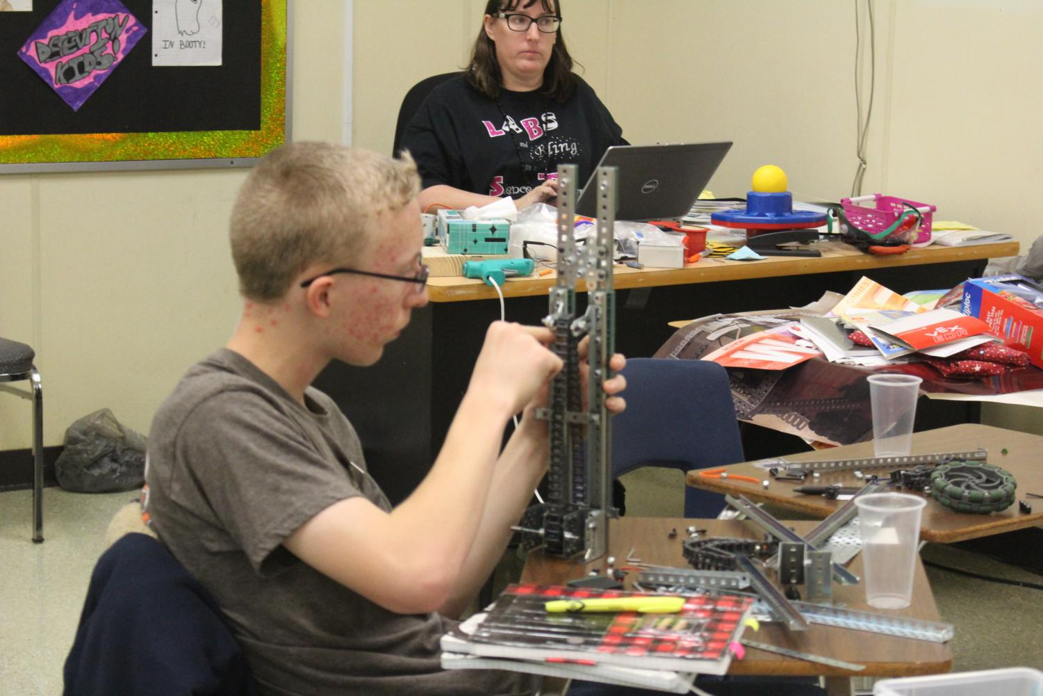 Jason Allison works on his robot while Mrs. Mock looks on. All the building for competition has to be done by the students with adult supervision.