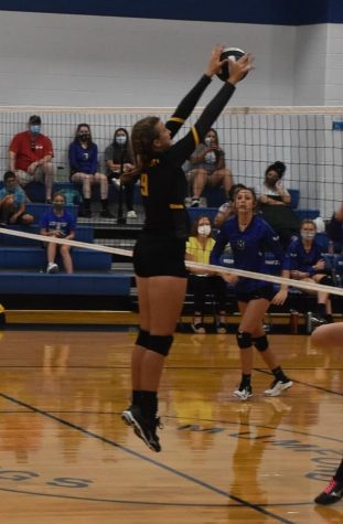 Emma Hering blocks a spike from Mumford during the varsity